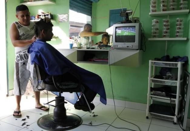 cortes de pelo sileño barbero de un ventilador mientras ven un programa de televisión del partido de la FIFA 2010 Copa Mundial de fútbol entre sil y Chile, en Sao Paulo