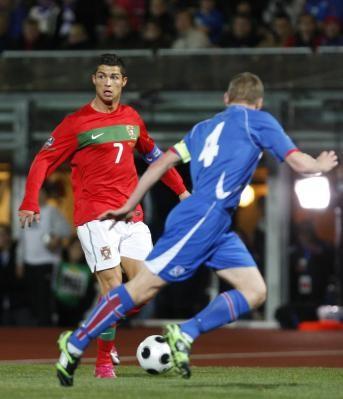 Cristiano Ronaldo controla el balón cerca de Kristjan Orn Sigurosson de Islandia durante su partido de fútbol Euro 2012 calificación en Reykjavik