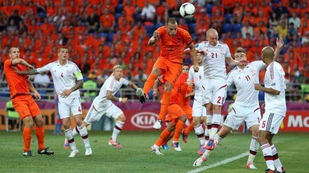 Heitinga remata de cabeza un balón ante Dinamarca