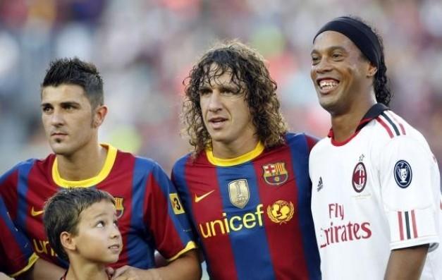jugador del AC Milán Ronaldinho posa con los jugadores del Barcelona Carles Puyol y David Villa en Barcelona